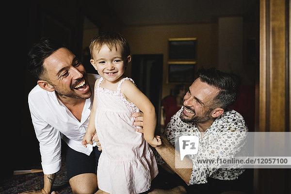 Glückliches schwules Paar  das mit seiner kleinen Tochter zu Hause spielt.