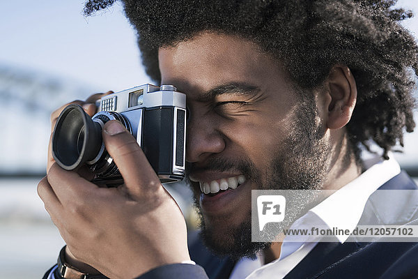 Close-up of smiling man taking a picture with a vintage camera