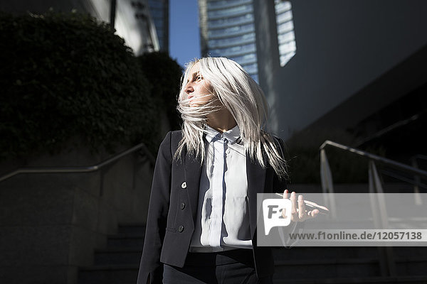 Young businesswoman with windswept hair in the city