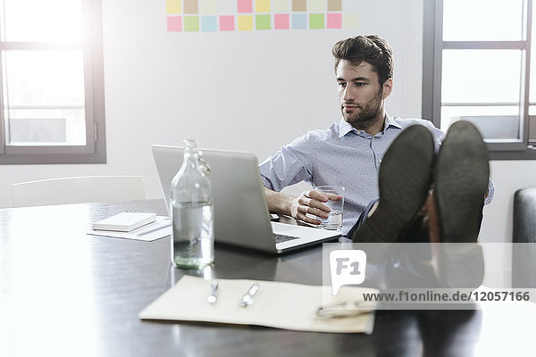 Young businessman working in office with feet on desk