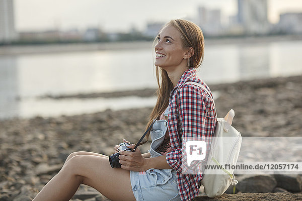 Smiling young woman with a camera sitting on stony beach