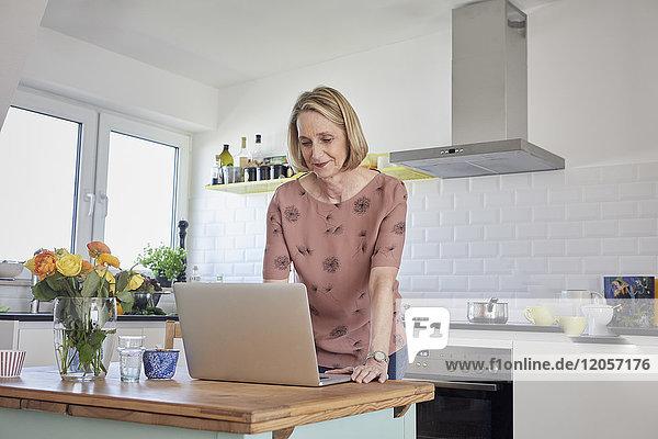 Reife Frau zu Hause mit Laptop in der Küche