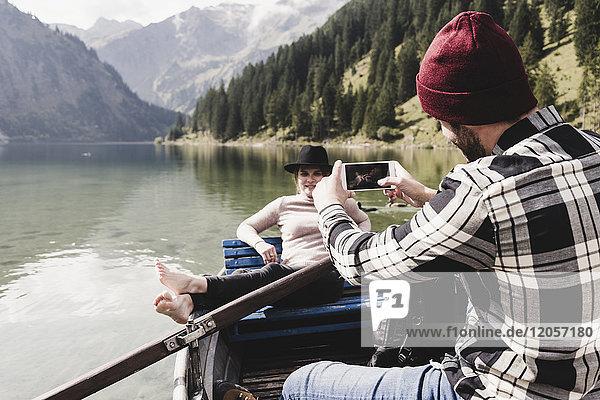Österreich  Tirol  Alpen  Mann macht Handyfoto von Frau im Ruderboot auf dem Bergsee