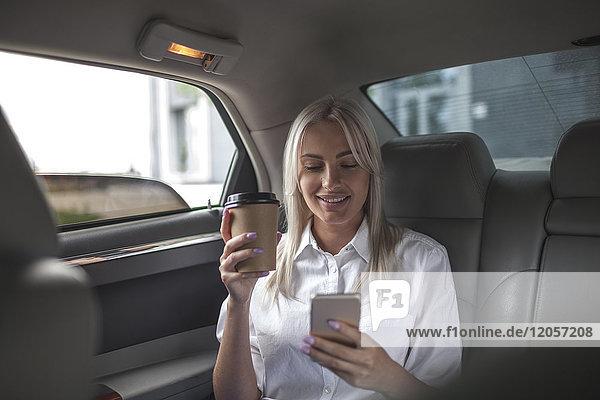 Lächelnde Geschäftsfrau mit Kaffee zum Mitnehmen und Handy im Auto