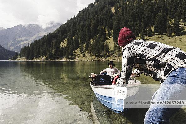 Österreich  Tirol  Alpen  Paar mit Ruderboot auf dem Bergsee