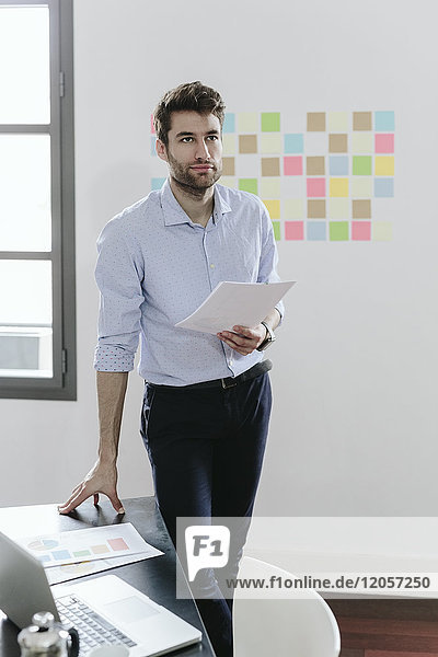 Young businessman working in office  holding documents