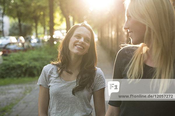 Zwei glückliche junge Frauen im Freien bei Sonnenuntergang Zwei glückliche junge Frauen im Freien bei Sonnenuntergang