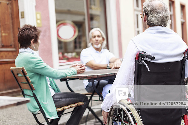 Deutschland  Heidelberg  Senior im Rollstuhl mit Freunden in einem Straßencafé