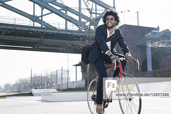 Lächelnder Geschäftsmann beim Fahrradfahren an der Flussbrücke