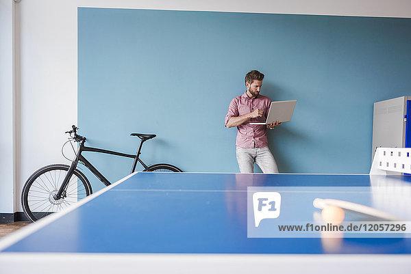 Mann mit Laptop im Pausenraum des modernen Büros