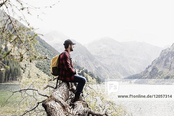 Österreich  Tirol  Alpen  Wanderer sitzend auf Baumstamm am Bergsee