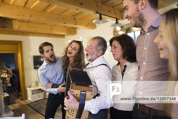 Senior Mann spielt Akkordeon für glückliche Familie