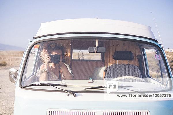 Spanien  Teneriffa  Frau im Transporter sitzend fotografiert mit Kamera