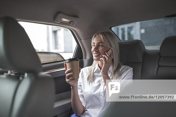 Smiling businesswoman with takeaway coffee on cell phone in car