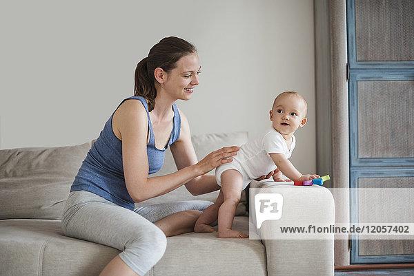 Glückliches kleines Mädchen mit Mutter  die auf der Couch spielt