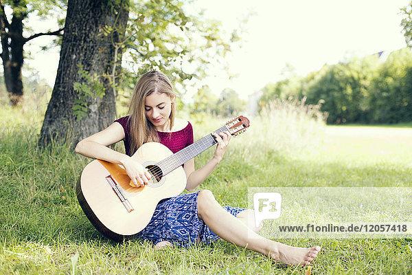 Junge Frau auf der Wiese sitzend  Gitarre spielend