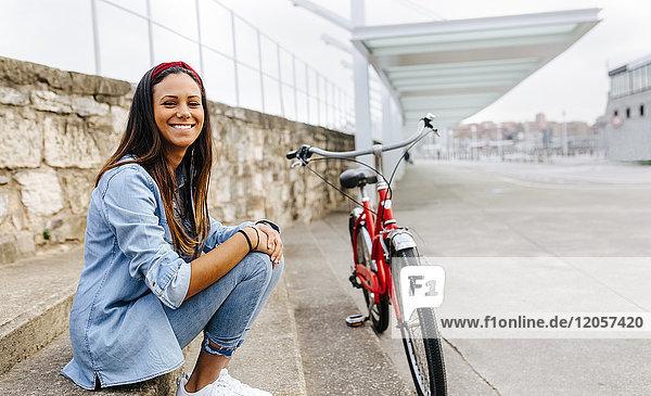 Spanien  Gijon  Porträt einer hübschen jungen Frau mit ihrem Fahrrad in der Stadt