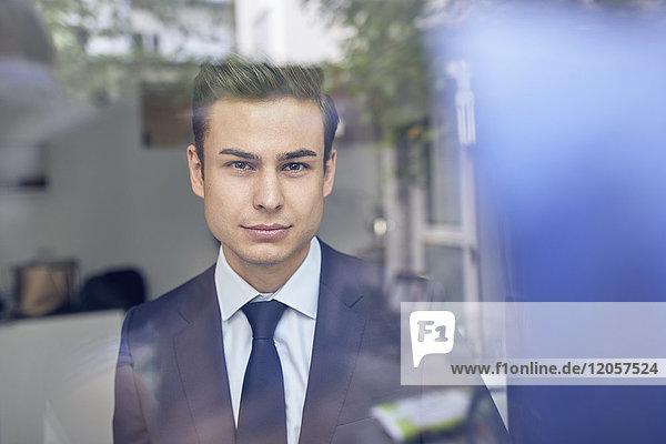 Jungunternehmer hinter Glasscheibe im Büro