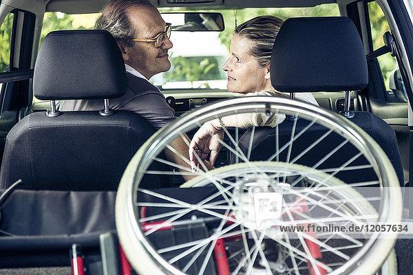 Lächelndes Paar im Auto mit Rollstuhl im Kofferraum