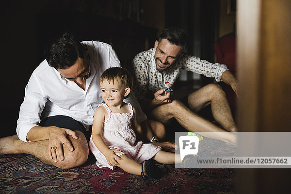 Gay couple playing with their little daughter at home