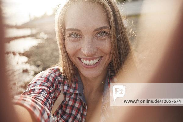 Porträt einer glücklichen jungen Frau am Flussufer