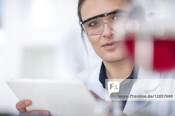 Wissenschaftler  der im Labor arbeitet und eine Tablette in der Hand hält.