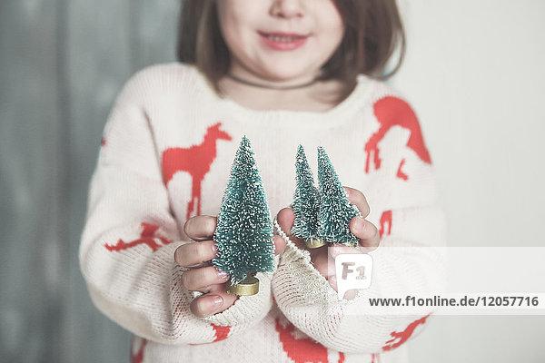 Kleines Mädchen mit Miniatur-Weihnachtsbaum  Nahaufnahme