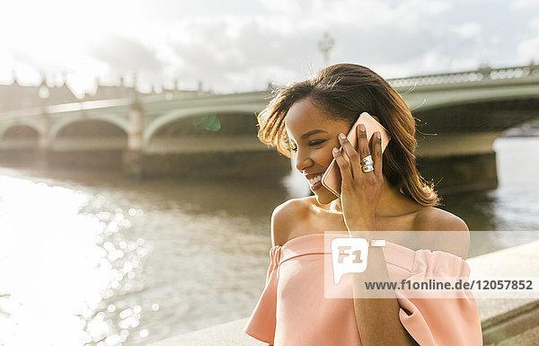 UK  London  Frau am Telefon in der Nähe der Westminster Bridge
