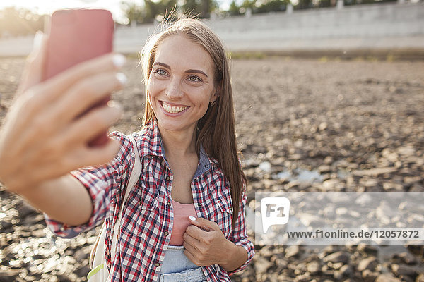Portait of happy young woman on cell phone at the riverside