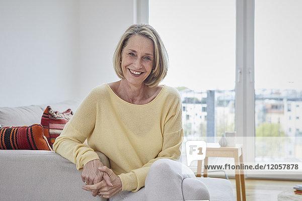 Porträt der glücklichen reifen Frau zu Hause auf dem Sofa