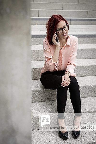 Junge Geschäftsfrau auf der Treppe sitzend  telefonierend