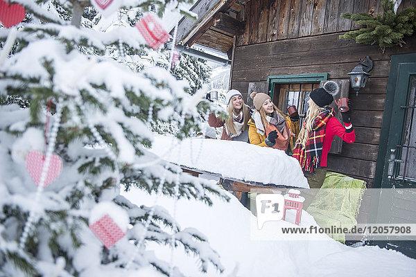 Österreich  Altenmarkt-Zauchensee  weibliche Freunde feiern im Holzhaus zur Weihnachtszeit