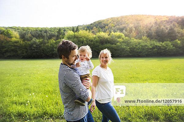 Eltern  die mit einem kleinen Jungen auf der Wiese spazieren gehen.