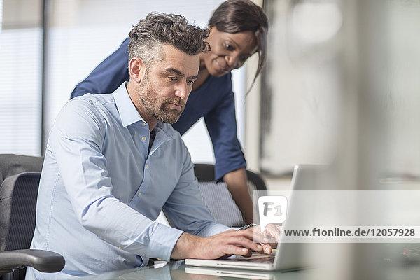 Kollegen bei der Arbeit am Laptop im Büro