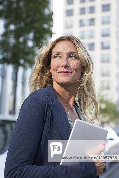 Lächelnde Geschäftsfrau mit Tablette in der Stadt