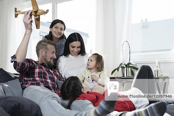 Eltern und drei Töchter beim Spielen mit dem Spielzeugflugzeug auf dem Sofa