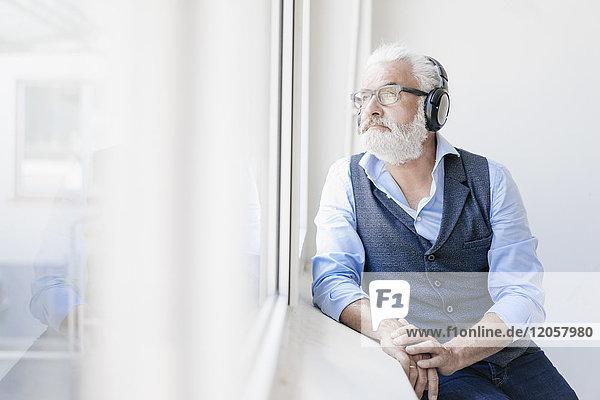 Erwachsener Mann mit Brille und Kopfhörer  der aus dem Fenster schaut.