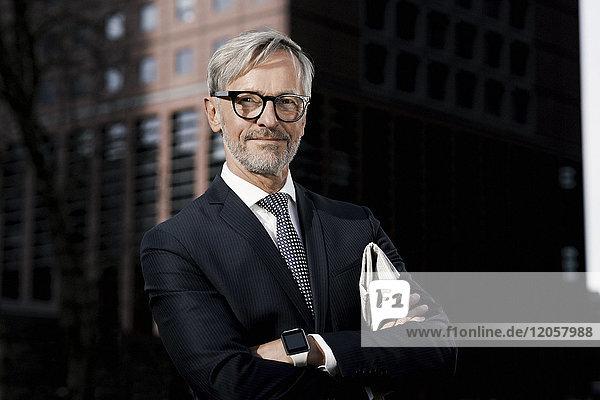 Porträt eines selbstbewussten grauhaarigen Geschäftsmannes im Freien
