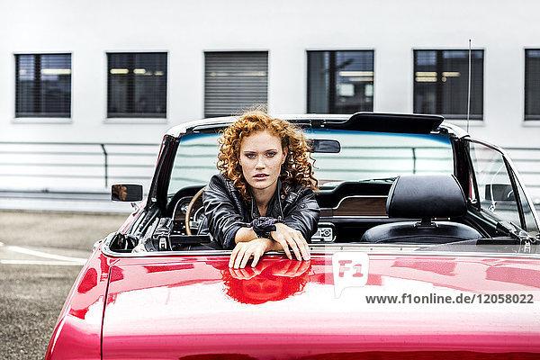 Porträt einer selbstbewussten rothaarigen Frau im Sportwagen