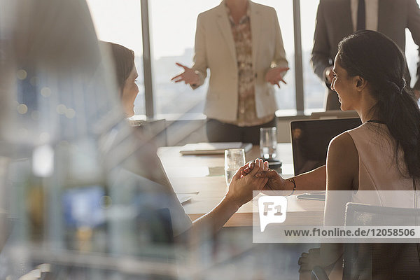 Businesswomen shaking hands in conference room meeting