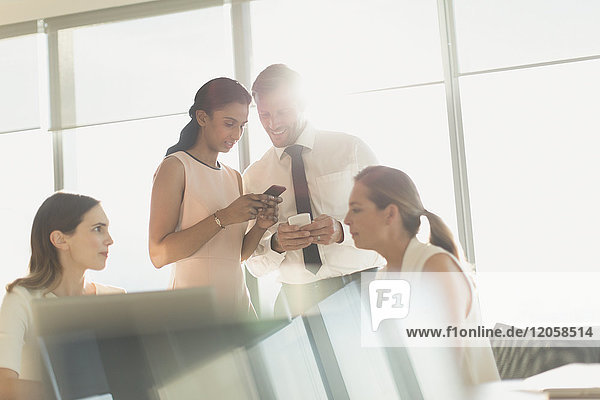Business people texting with cell phones in sunny conference room meeting
