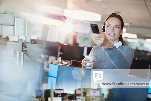 Businesswoman using remote control  drinking coffee in office