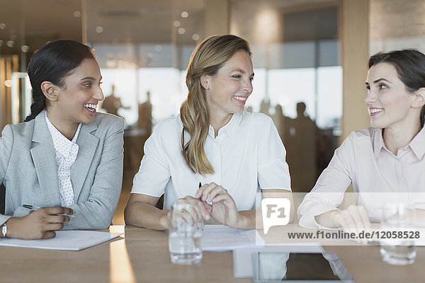 Smiling businesswomen talk in conference room meeting