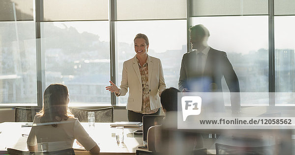 Businesswoman talking  leading meeting in sunny conference room
