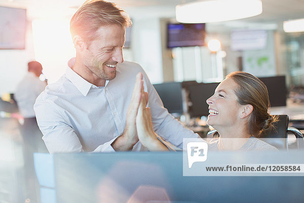 Businessman and businesswoman high-fiving at computer in office