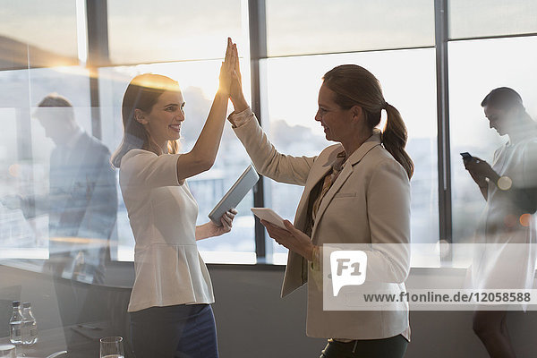 Businesswomen with digital tablets high-fiving in conference room