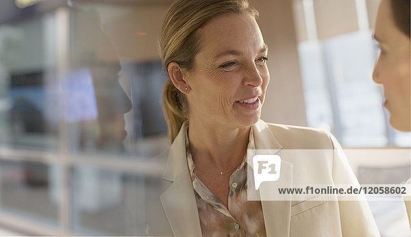 Smiling businesswoman talking to colleague