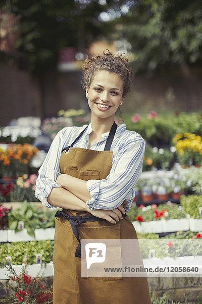Portrait lächelnde  selbstbewusste Floristin im Blumenladen
