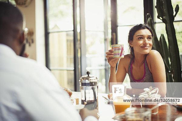Lächelnde Frau beim Kaffeetrinken am Frühstückstisch