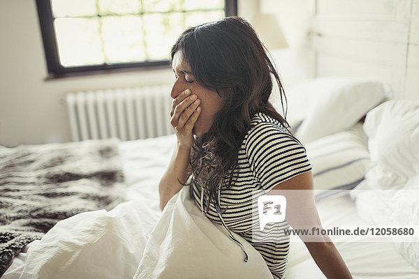 Müde junge Frau gähnt im Bett